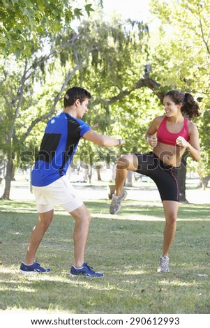 Young Woman Working With Personal Trainer In Park - stock photo