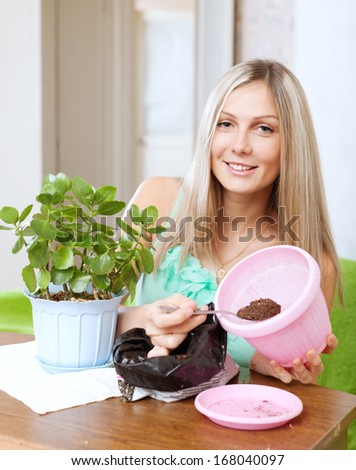 Young woman works with  flower pots at her home - stock photo