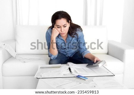 young woman worried at home in stress at living room accounting debt bills expenses with calculator feeling desperate on payments in bad financial situation concept - stock photo
