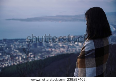 Young woman wrapped in plaid looking at the city from hill in night. Concept of tranquil life from the urban bustle - stock photo