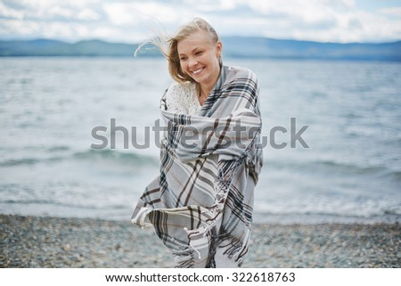 Young woman wrapped in plaid standing by the seaside - stock photo