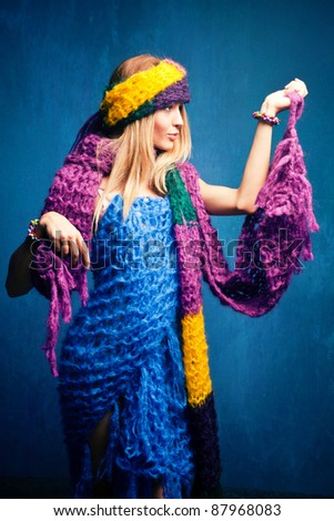 young woman wrapped in wool scarfs, studio shot - stock photo