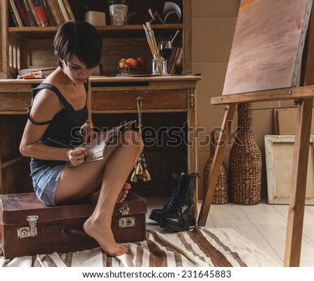 Young woman writes diary in her art studio.She sitting in her art studio.Fashion art image concept. - stock photo
