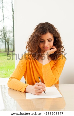 Young woman writing a letter - stock photo