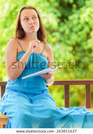 Young woman writing to notebook. Outdoor portrait. - stock photo