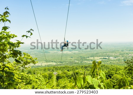 Young woman zip-lining with aerial countryside view at Blue Mountain, Ontario, Canada. - stock photo