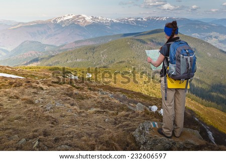 Young women backpacker standing on top of the mountain and looking to the map. Freedom concept. Autumn mountain travel.  - stock photo