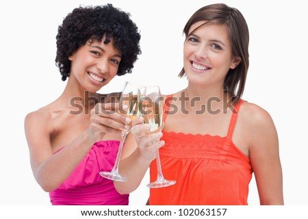 Young women clinking glasses of champagne in order to celebrate an event - stock photo