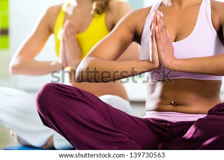 Young women doing yoga and meditation in gym for better fitness, caucasian and latina people - stock photo
