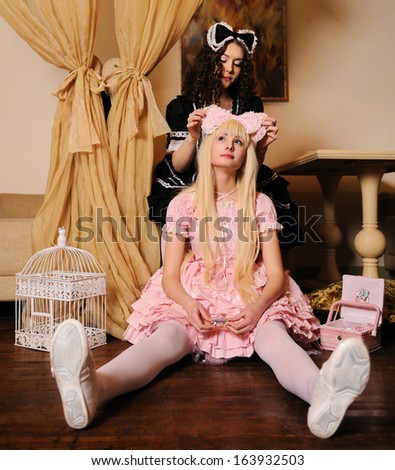 Young women dressed as dolls, sitting in the doll house. - stock photo