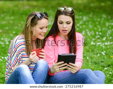 Young women drinking coffee and browsing internet on tablet at park and enjoying summer day - stock photo
