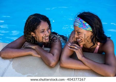 Young women enjoying in the swimming pool at resort - stock photo