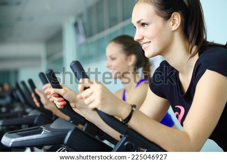 Young women exercising on stationary bicycles in fitness gym.  - stock photo