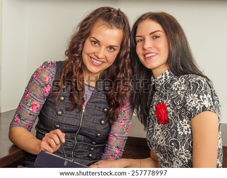 Young women friends chatting at home and using laptop to look at new photo or browsing internet for information - stock photo