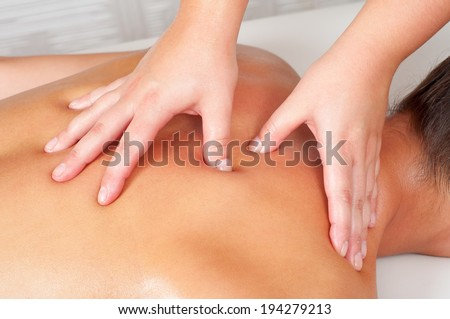 Young women getting back massage in massage salon. - stock photo