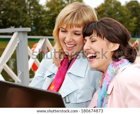Young women having conversation  laughing  with laptop outdoor. fall - stock photo
