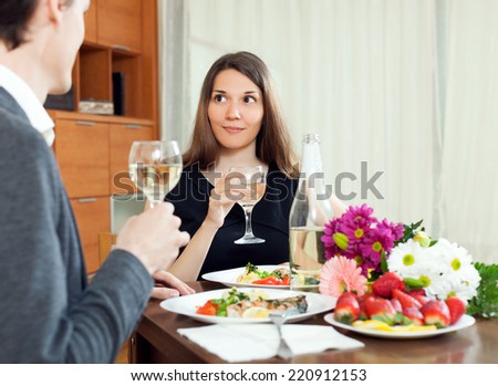 Young women having romantic dinner with her husband and drinking champagne together in home - stock photo