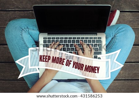 Young women holding laptop writen Keep More Of Your Money on it - stock photo