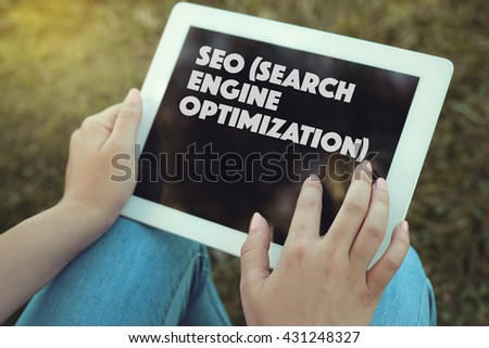 Young women holding tablet writen Seo (Search Engine Optimization) on it - stock photo