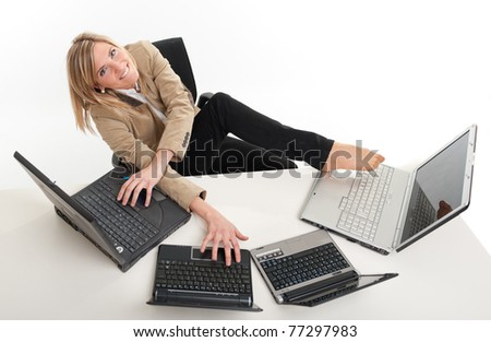 Young women in a desk overcrowded with computers typing with both hands and feet - stock photo