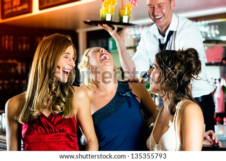 Young women in bar or club having fun and laughing, the bartender serve cocktails - stock photo