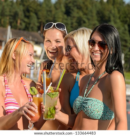 Young women in bikinis having fun with cocktails during summer - stock photo