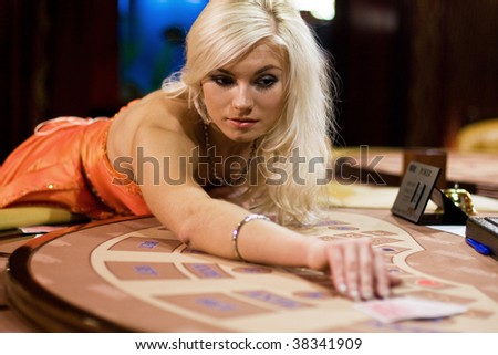 young women in casino takes playing cards - stock photo
