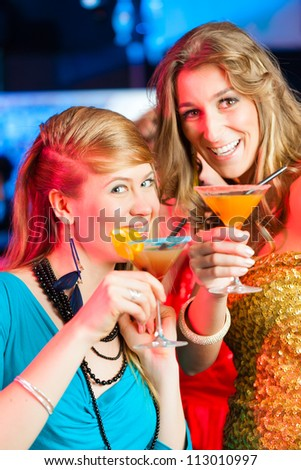 Young women in club or bar drinking cocktails and having fun - stock photo