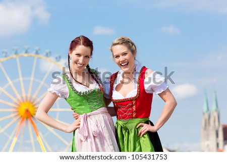 Young women in traditional Bavarian clothes - dirndl or tracht - on a festival or Oktoberfest - stock photo