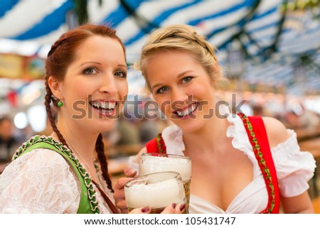 Young women in traditional Bavarian clothes - dirndl or tracht - on a festival or Oktoberfest in a beer tent - stock photo