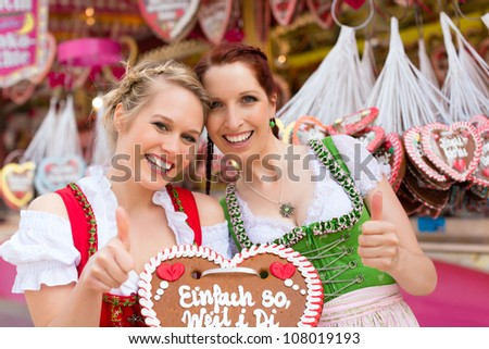 Young women in traditional Bavarian clothes - dirndl or tracht -with a gingerbread souvenir heart on a festival or Oktoberfest - stock photo