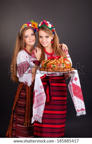 Young women in ukrainian clothes, with garland and round loaf on black background - stock photo