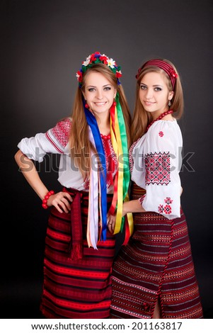 Young women in ukrainian clothes, with garland  on black background - stock photo