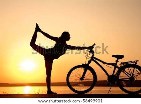 Young women is engaged in yoga on  sunset with bike - stock photo