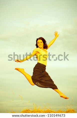 Young women jumping on a field in rural areas. Old toned image - stock photo