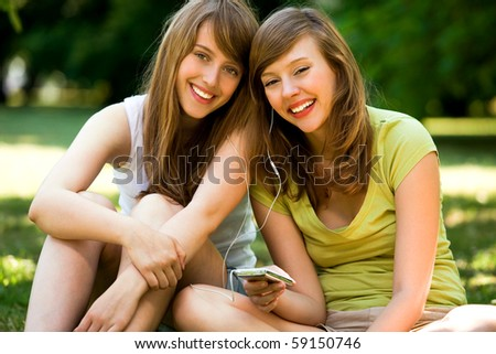 Young women listening to MP3 player - stock photo
