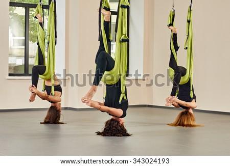 Young women making upside down antigravity yoga exercises. green hammocks - stock photo