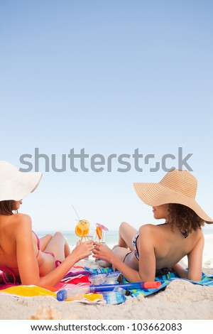 Young women on beach towels clinking their glasses while looking at each other - stock photo