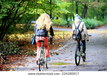 Young women on bicycles in the park - stock photo
