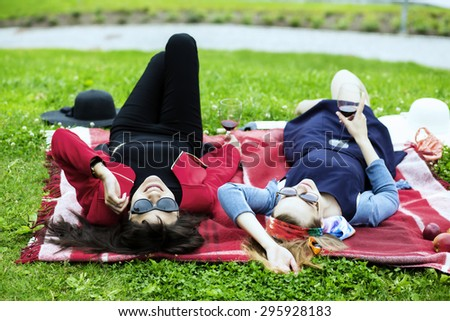 Young women on the red picnic blanket - stock photo