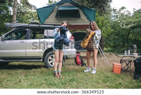 Young women opening sleeping bags in campsite - stock photo