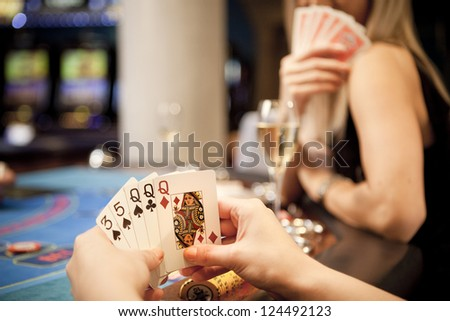 Young women playing poker in the casino - stock photo