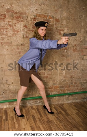 young women policeman fulfils receptions of shooting from a pistol - stock photo