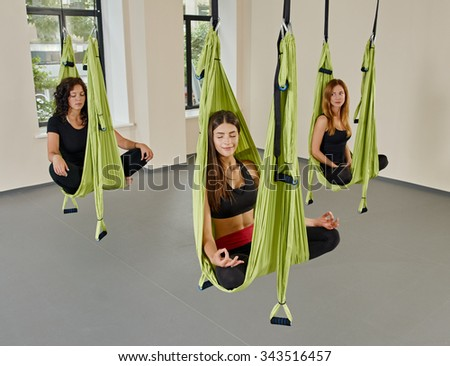 Young women posing in anti-gravity aerial yoga green hammock. indoor fitness club. break relax. shot from above  - stock photo