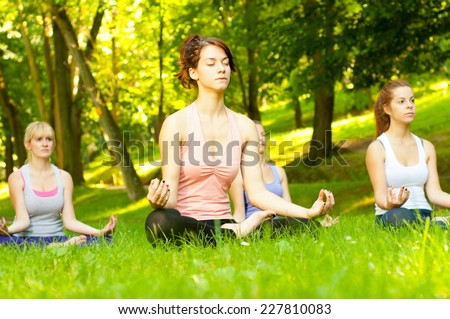 Young women practicing yoga in the park. - stock photo