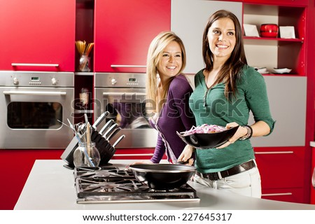Young women preparing meal in the kitchen - stock photo