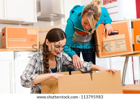 Young women - presumably friends - with moving box in her house moving in or out of a apartment, focus on moving box - stock photo