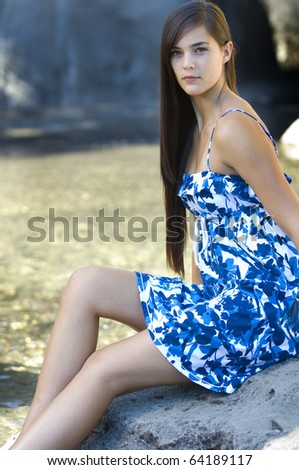 Young women resting near stream wearing blue dress - stock photo