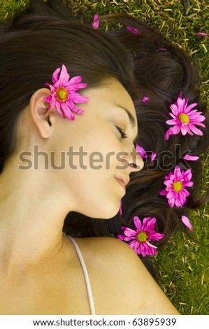 Young women resting near stream with flowers in hair - stock photo
