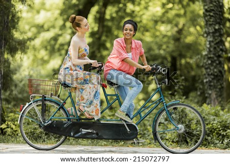 Young women riding on the bicycle - stock photo